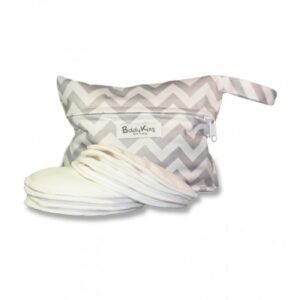 Set of 8 white cotton circular breast/chest pads piled in front of a grey and white zig-zag print waterproof carrier bag