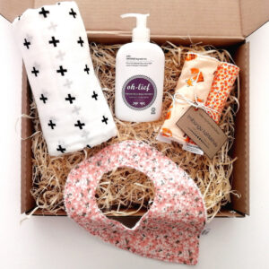 Gift box containing a white muslin with black cross print, pink and grey floral baby bib, orange fox-themed burp cloth set (2) and 200ml bottle of natural baby wash