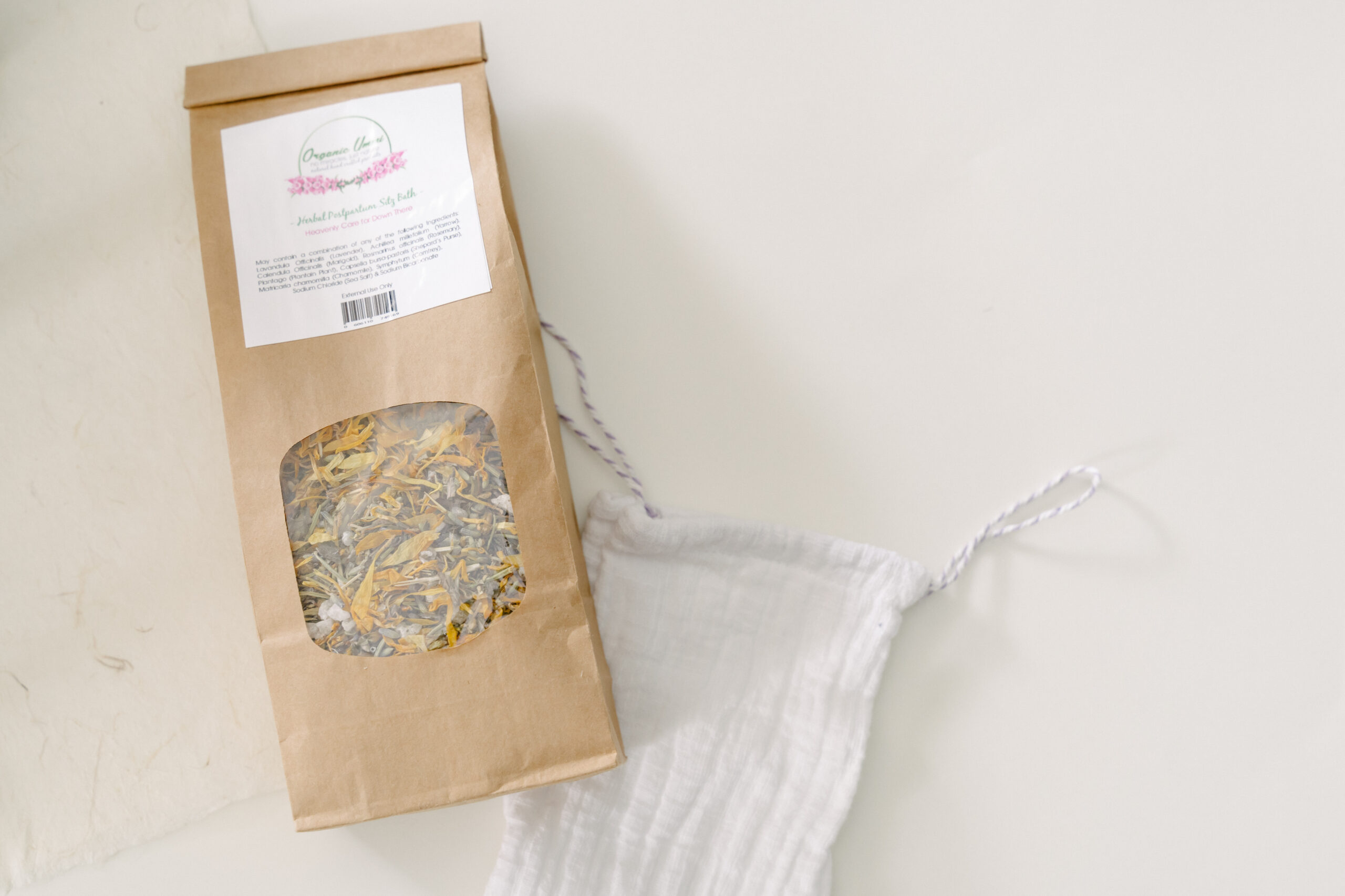 Brown bag containing a mixture of herbs, labelled herbal sitz bath mix lying beside a small white muslin bag